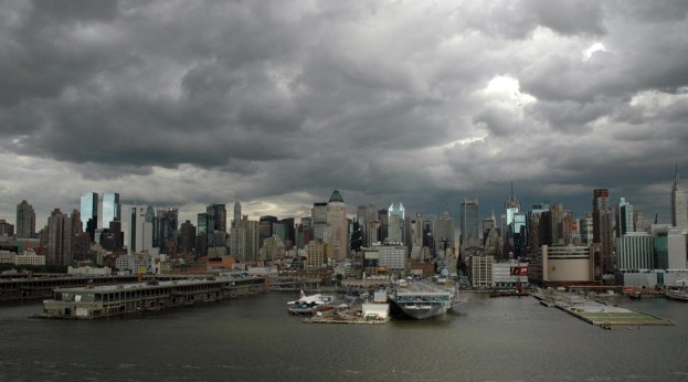 Here's a view of the lower Manhattan skyline on a cloudy afternoon as we left on a cruise to Canada in 2005. The dull gray of the clouds nicely matches the dull gray of the water. In the center of the frame is the Intrepid Sea, Air & Space Museum at Pier 89. The museum was closed the next year for renovations to the displays, including the USS Intrepid.