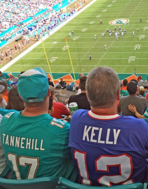 For two friends at the Oct. 23, 2016, football game between our Miami Dolphins and the Buffalo Bills at the Hard Rock Stadium brought out friends with different teams. Here you see two friends with different loyalties – the guy to the left with his Dolphins Ryan Tannehill jersey (Tannehill is the current starting quarterback for Miami) an the other with his Bills jersey honoring NFL Hall of Famer Jim Kelly.