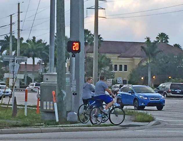 """It's nice that they have countdown clocks at intersections for pedestrians (or, in this case, bicyclists) to see just how long until the next light change. However, I think that such """"shot clocks"""" ought to be put up with the traffic signals so drivers will know when the next yellow light is coming – and they don't have to glance over to the side in hopes of catching a glimpse. I got this shot near our home in Naples, Fla., on Feb. 14, 2017."""